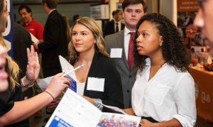 Several attendees listen to a recruiter at the Fall 2017 Career Fair at Coleman Coliseum.