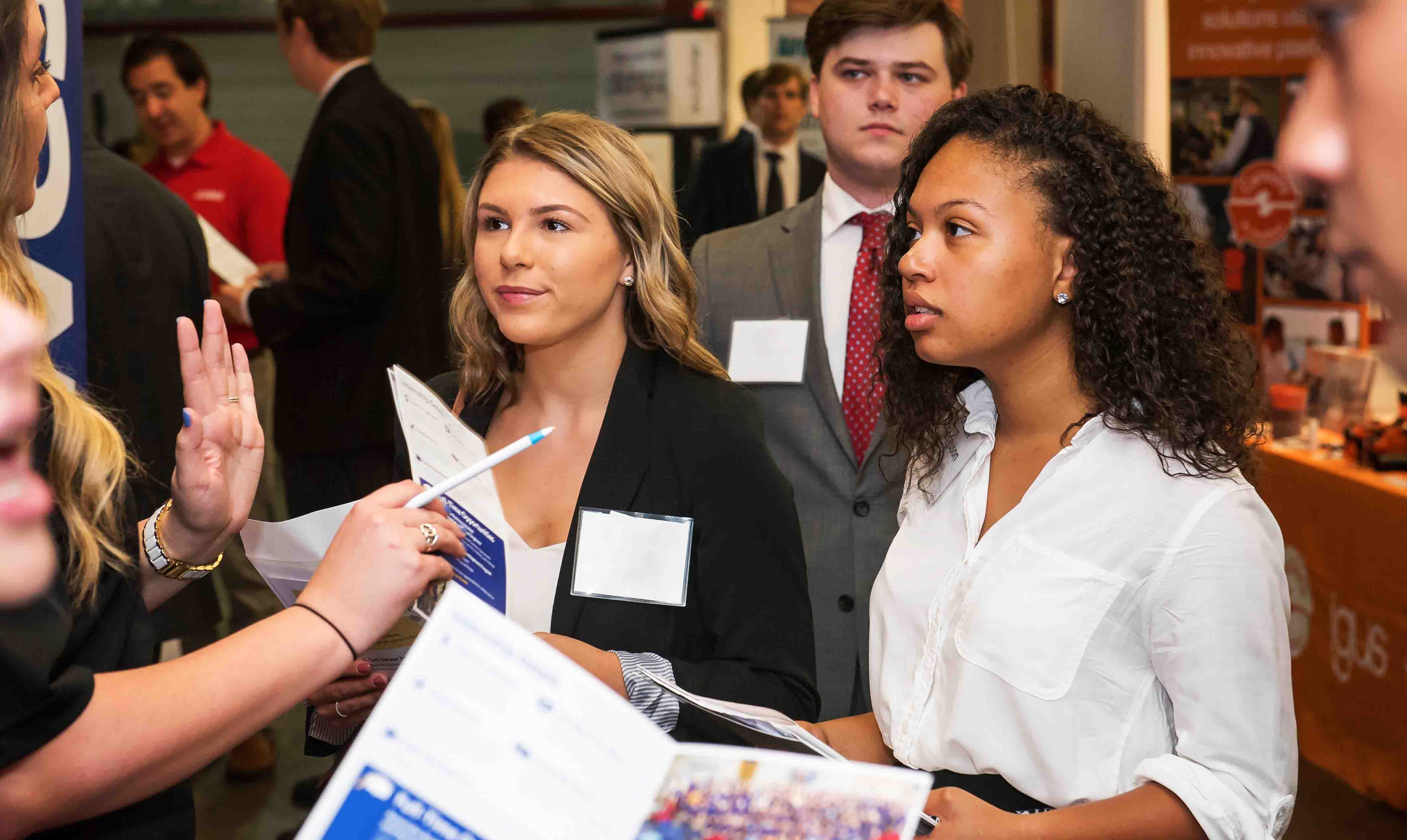 several attendees listen to a recruiter at the fall 2017 career fair at coleman coliseum