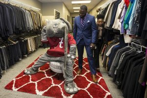 Chris McGee looks at Big Al inside the Crimson Career Closet with another student