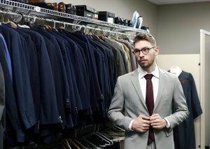 A student models a grey suit and crimson tie in the Crimson Closet