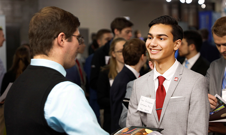 Student in a suit with a Crimson Tie interacts with Recruiter at Career Fair