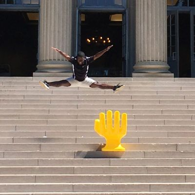 Handshake hand chair outside Gorgas Library with jumping student